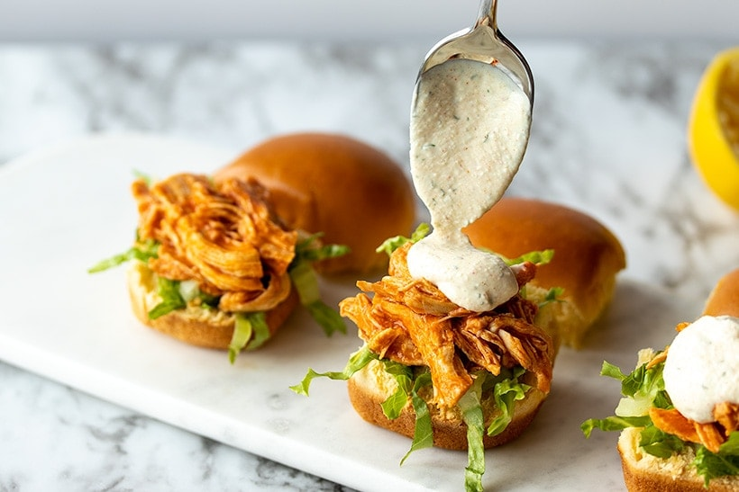 ranch dip being spooned onto buffalo chicken slider on a marble serving tray