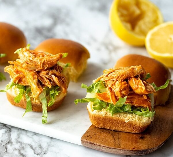 three buffalo chicken sliders on a marble serving tray with a cut lemon behind them