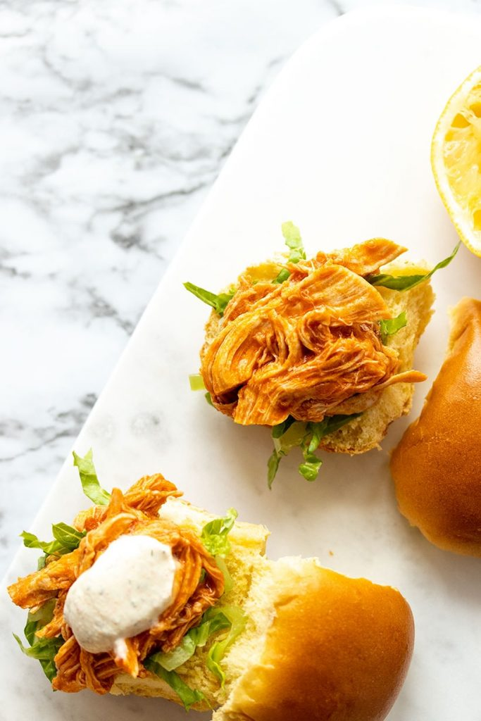 two buffalo chicken sliders on a marble serving tray viewed from overhead