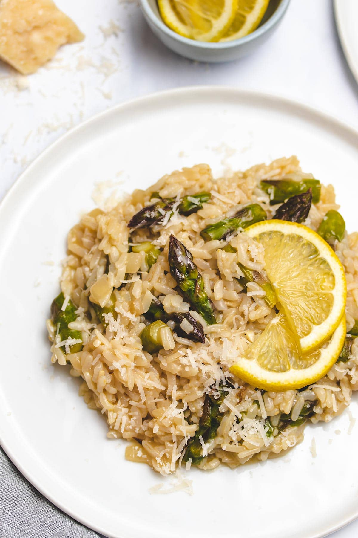 lemon asparagus risotto on a white plate garnished with lemon slices and parmesan cheese