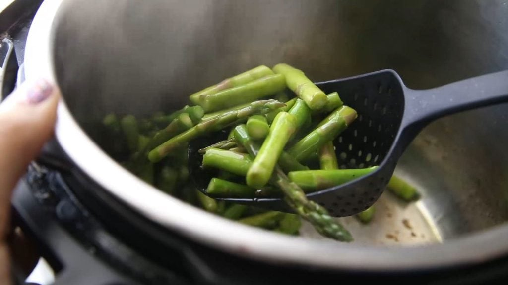 scooping sauteed asparagus out of the Instant Pot
