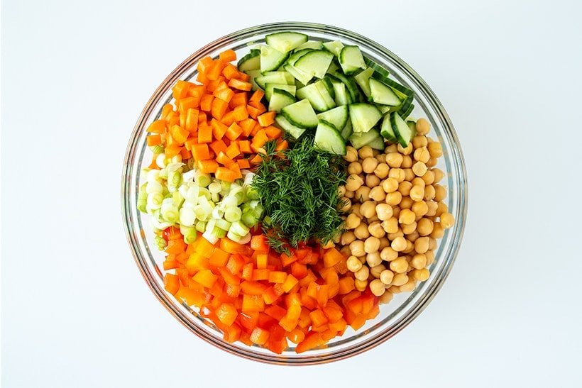 ingredients for quinoa chickpea salad displayed in large bowl