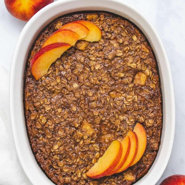 pan of baked vegan peaches and cream baked oatmeal with slice removed