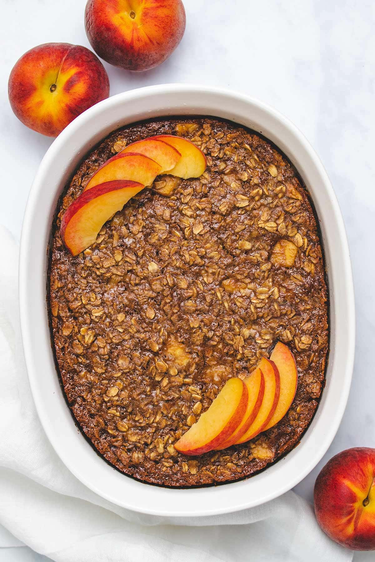 Vegan Peach Baked Oatmeal in a white casserole dish next to a white linen and 3 peaches