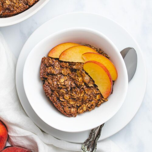 slice of vegan peaches and cream baked oatmeal on a white plate with two peach slices