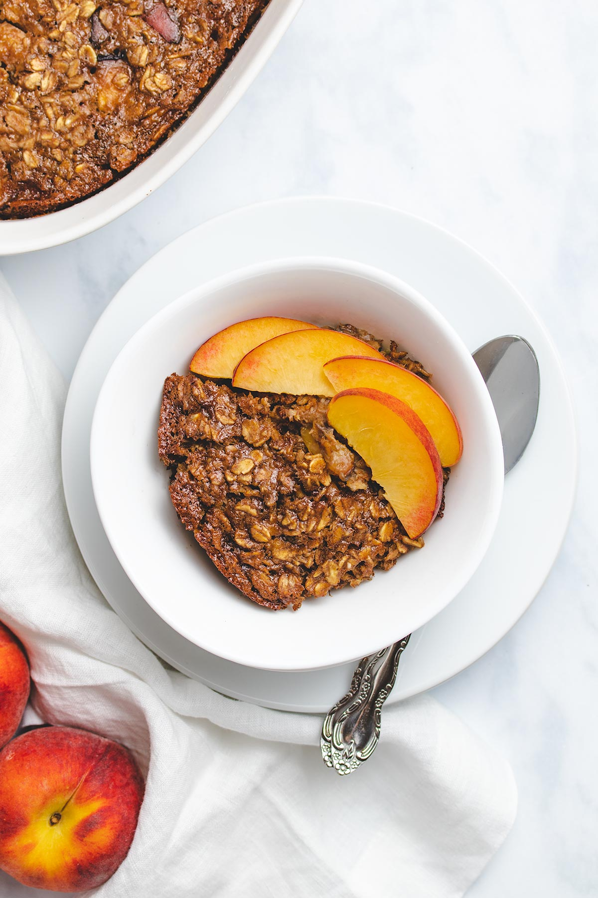 Vegan Peach Baked Oatmeal in a white bowl garnished with peach slices