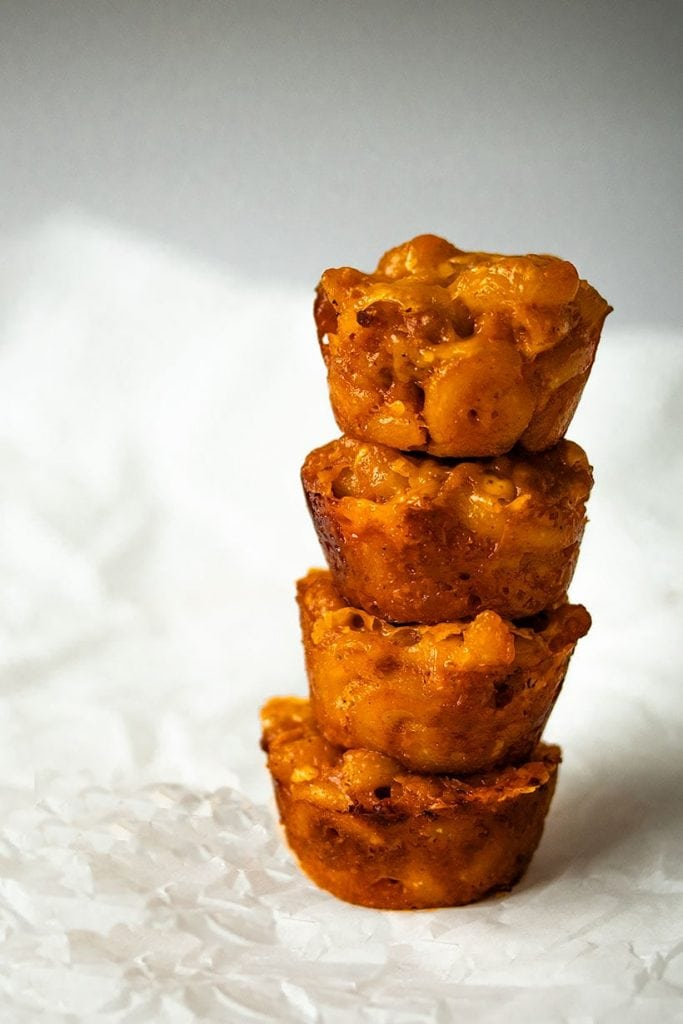 stack of four chili mac and cheese bites on a piece of parchment paper