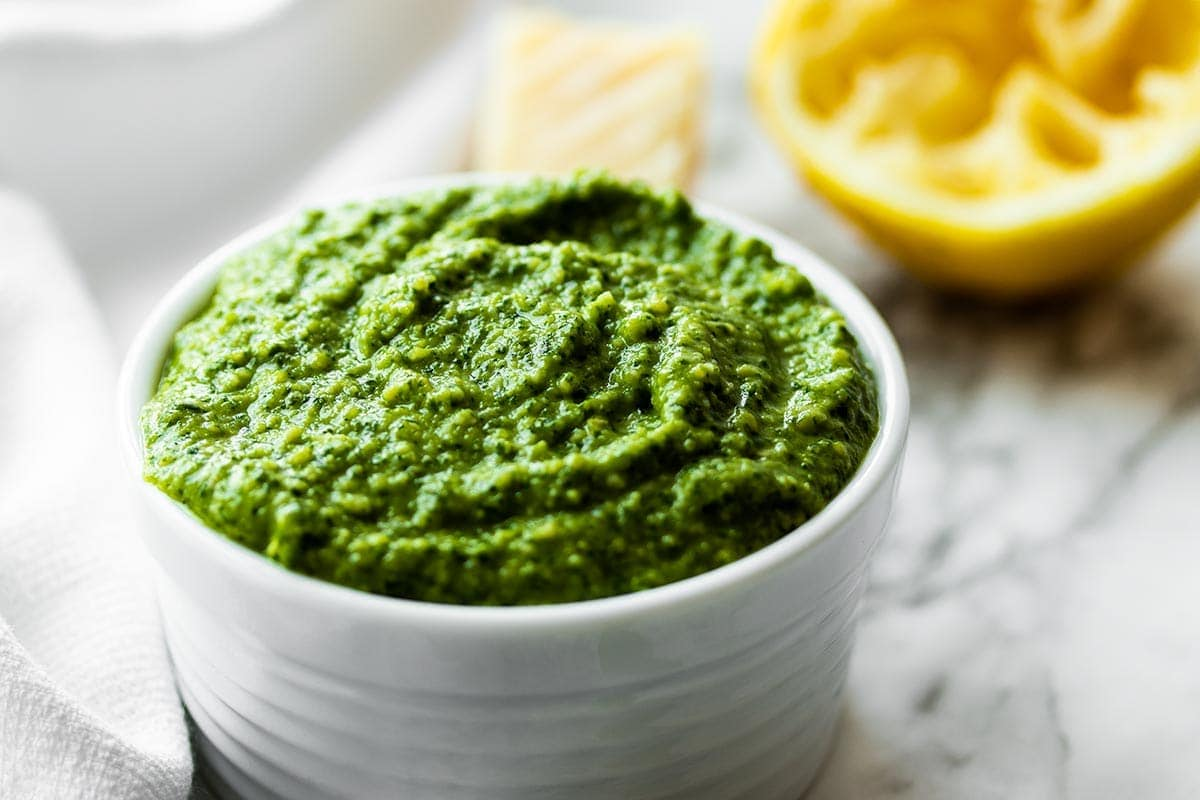 Cashew pesto in a white bowl with half a lemon in the background