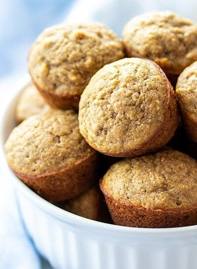 Mini Banana Muffins piled up in a white bowl next to a blue towel
