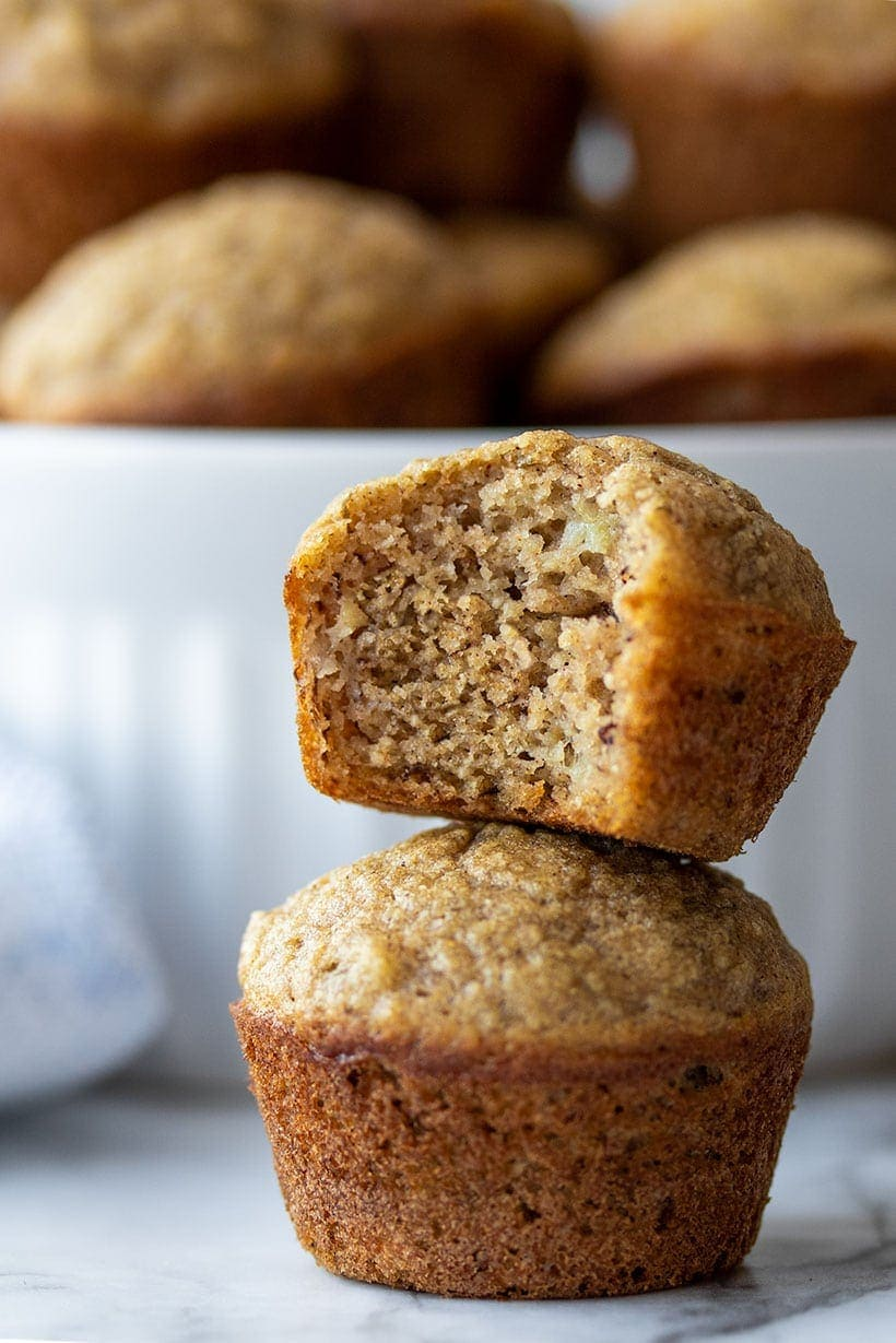 one mini muffin stacked on top of another with a bite out of it, in front of a white bowl with more mini muffins in it
