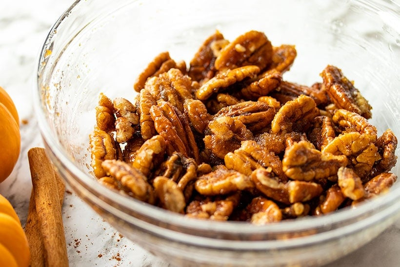 Pecans coated with brown sugar in a small glass bowl