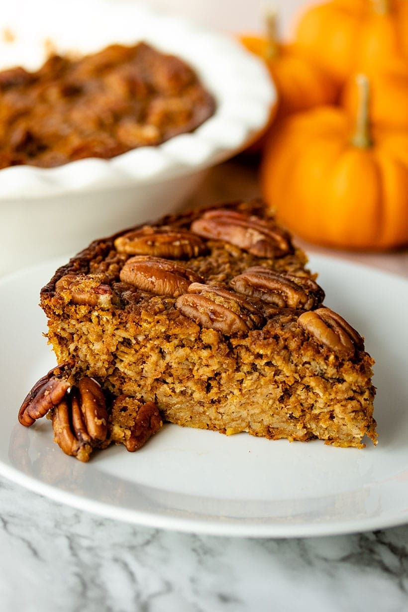 A slice of Pumpkin Spice Baked Oatmeal on a white plate in front of a pie dish and small pumpkins