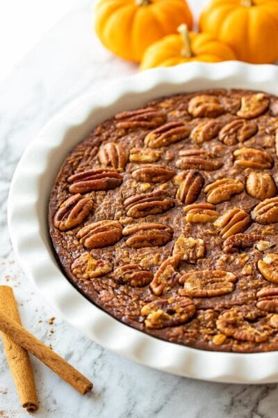 Pumpkin Spice Baked Oatmeal in a white pie dish next to three pumpkins and cinnamon sticks