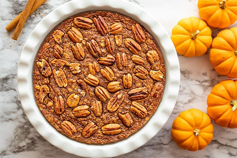 Pumpkin Spice Baked Oatmeal in a white pie dish next to pumpkins and cinnamon sticks viewed from overhead