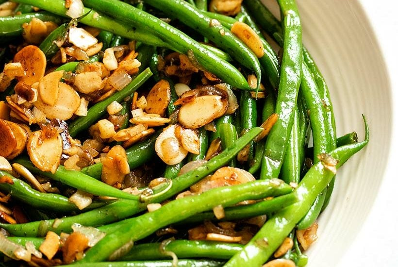 Green beans in almondine in a white serving dish