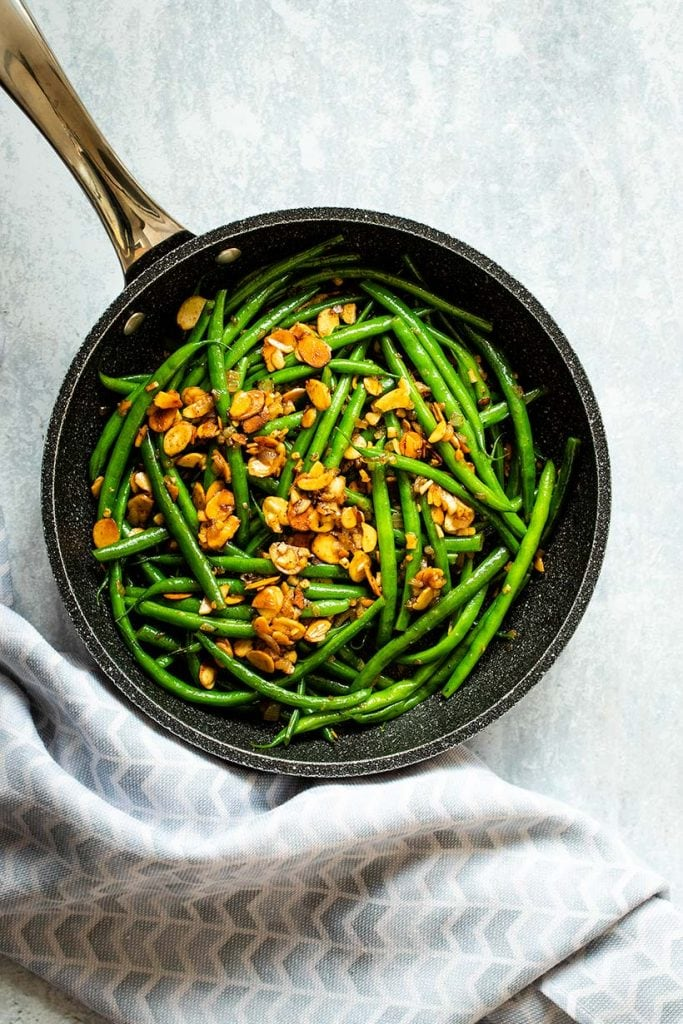 Green beans almondine in a black skillet next to a blue and white towel