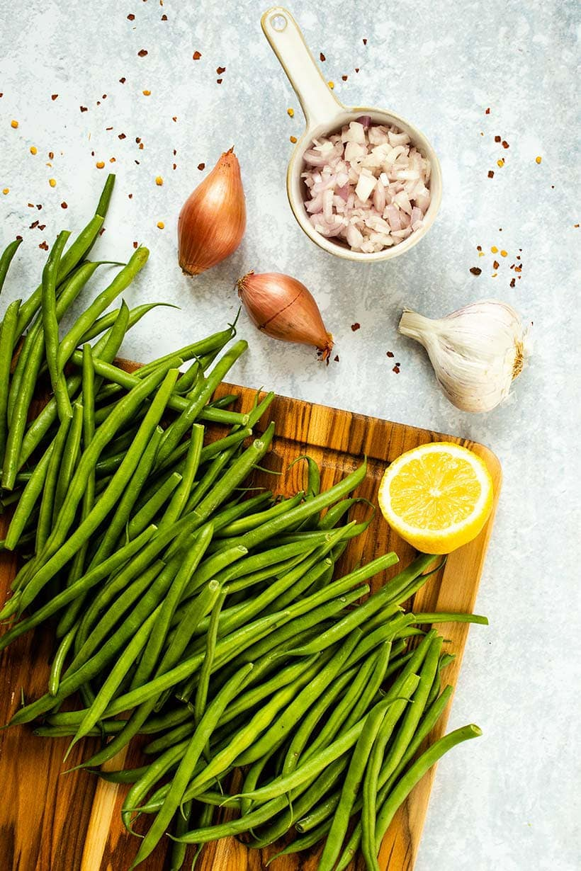 green beans on a wooden cutting board next to half a lemon, two whole shallots, a head of garlic and finely chopped shallots in a measuring cup