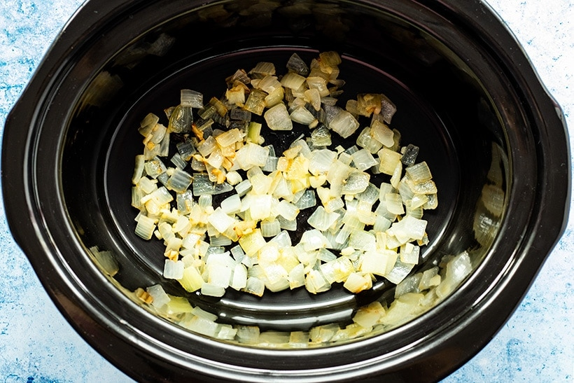 Sauteed onion, garlic and ginger in a slow cooker viewed from overhead