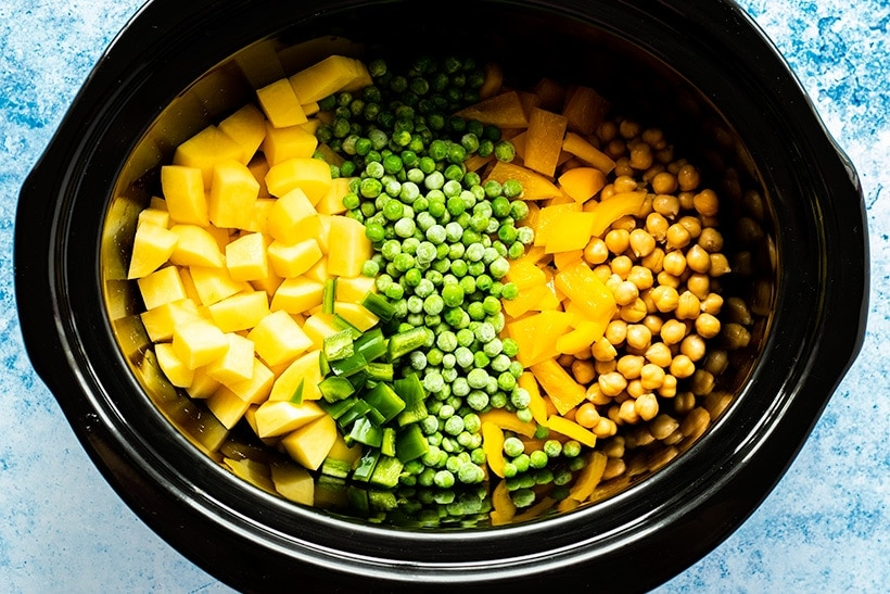 Potatoes, jalapeno, green peas, bell pepper and chickpeas in a slow cooker viewed from overhead