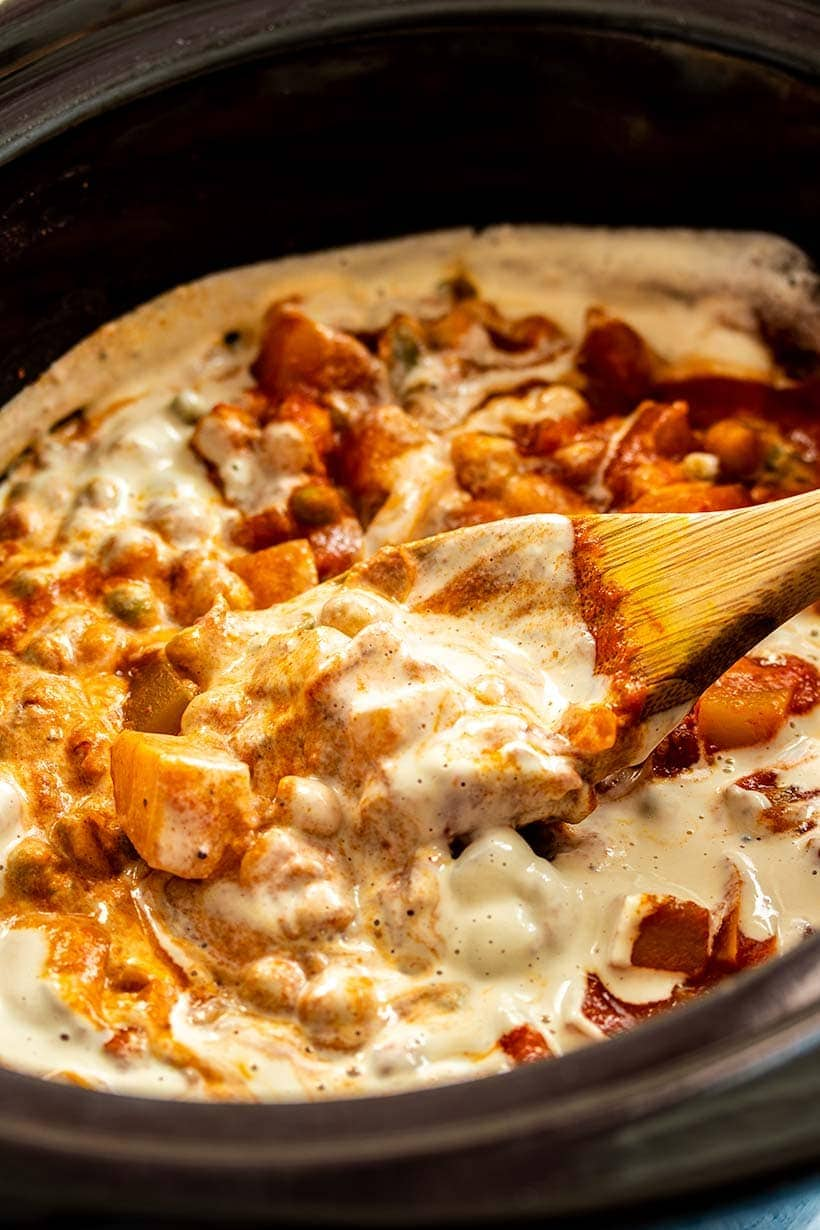 Stirring cashew cream into the potato and chickpea tikka masala