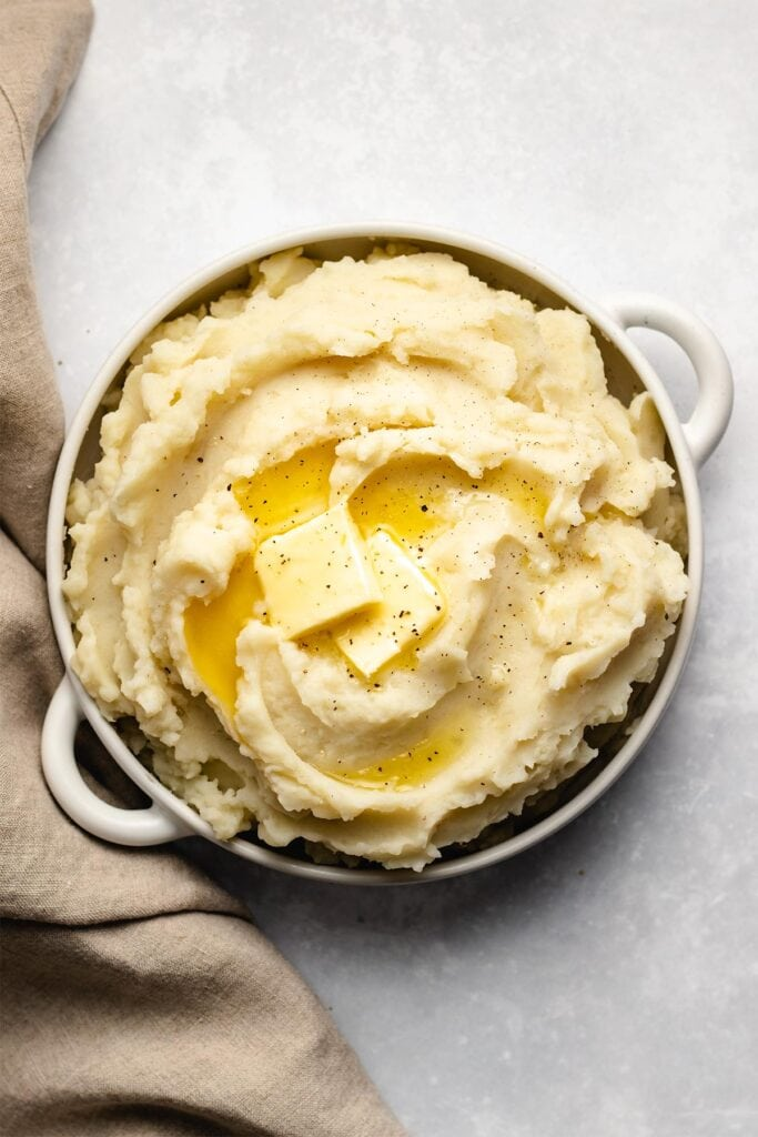 Butter melting on mashed potatoes in a white bowl