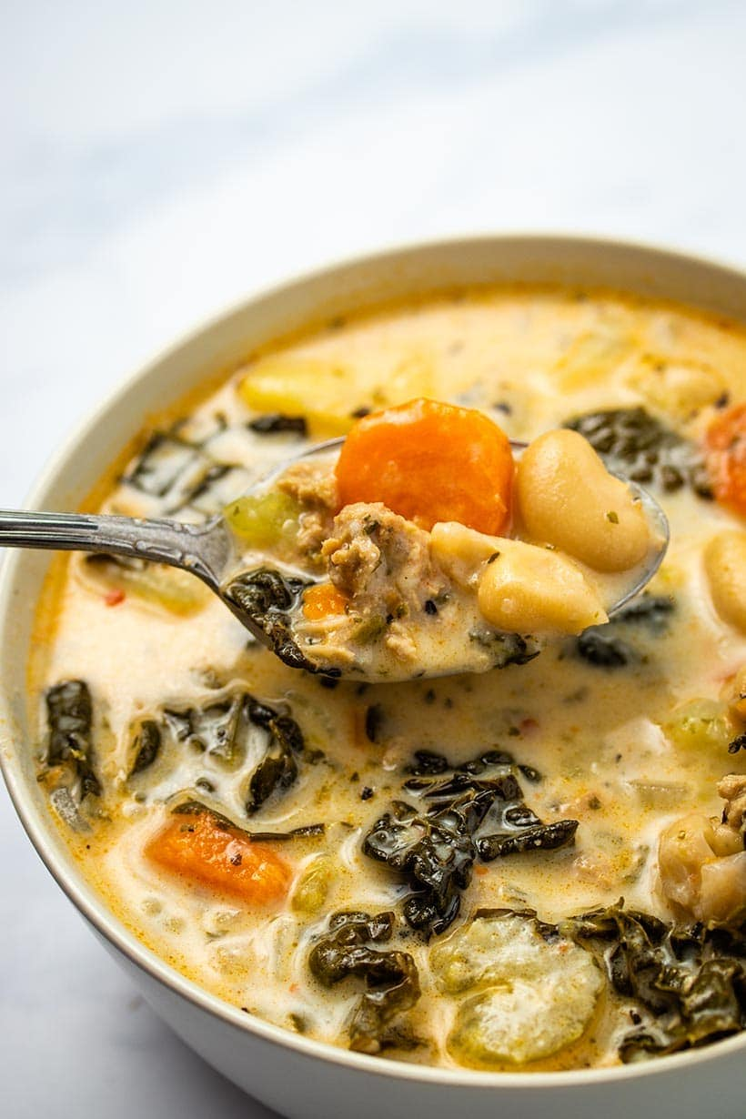 a spoonful of soup being held above a full bowl of zuppa toscana