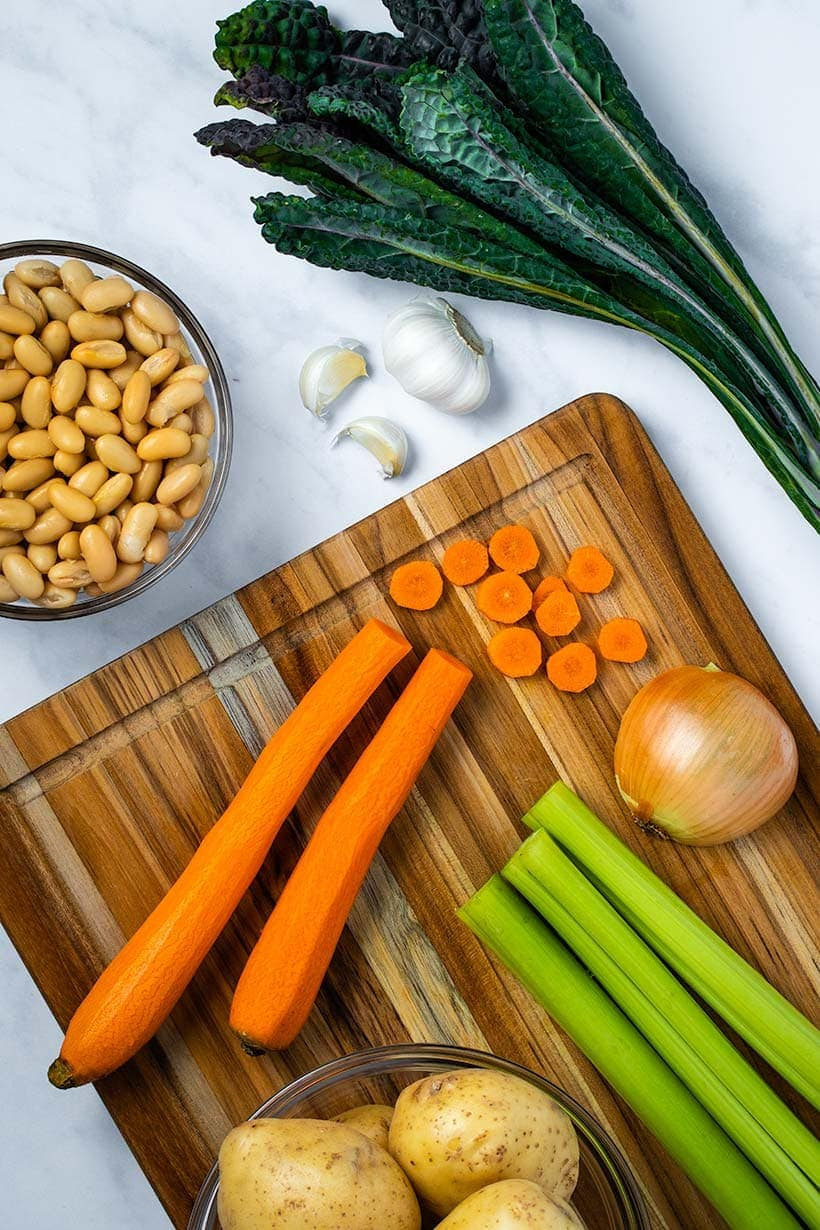 potatoes, carrots, celery, onion, kale, garlic and white beans on a wooden cutting board viewed from overhead