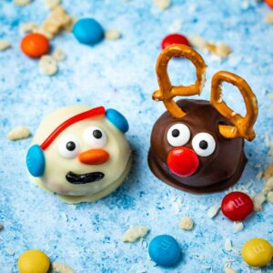 peanut butter ball snowman and reindeer on a blue background surrounded by puffed rice cereal and M&Ms