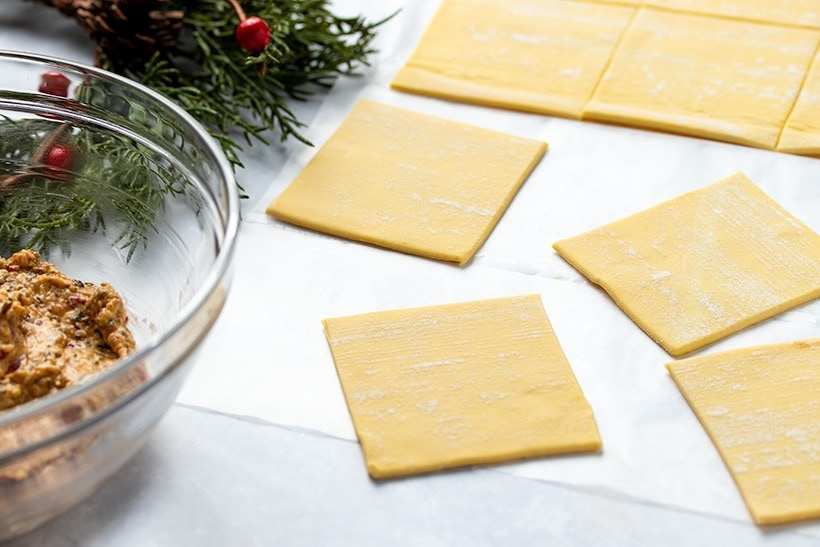 squares of puff pastry on parchment next to a bowl of goat cheese filling and festive greenery