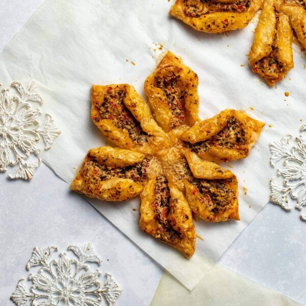pesto and goat cheese snowflake pastry on parchment next to white and gold snowflake ornaments