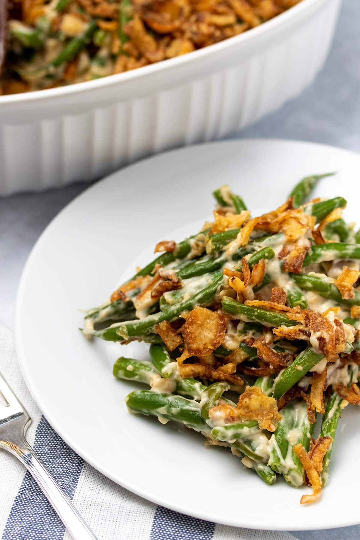 vegan green bean casserole on a white plate in front of a white casserole dish