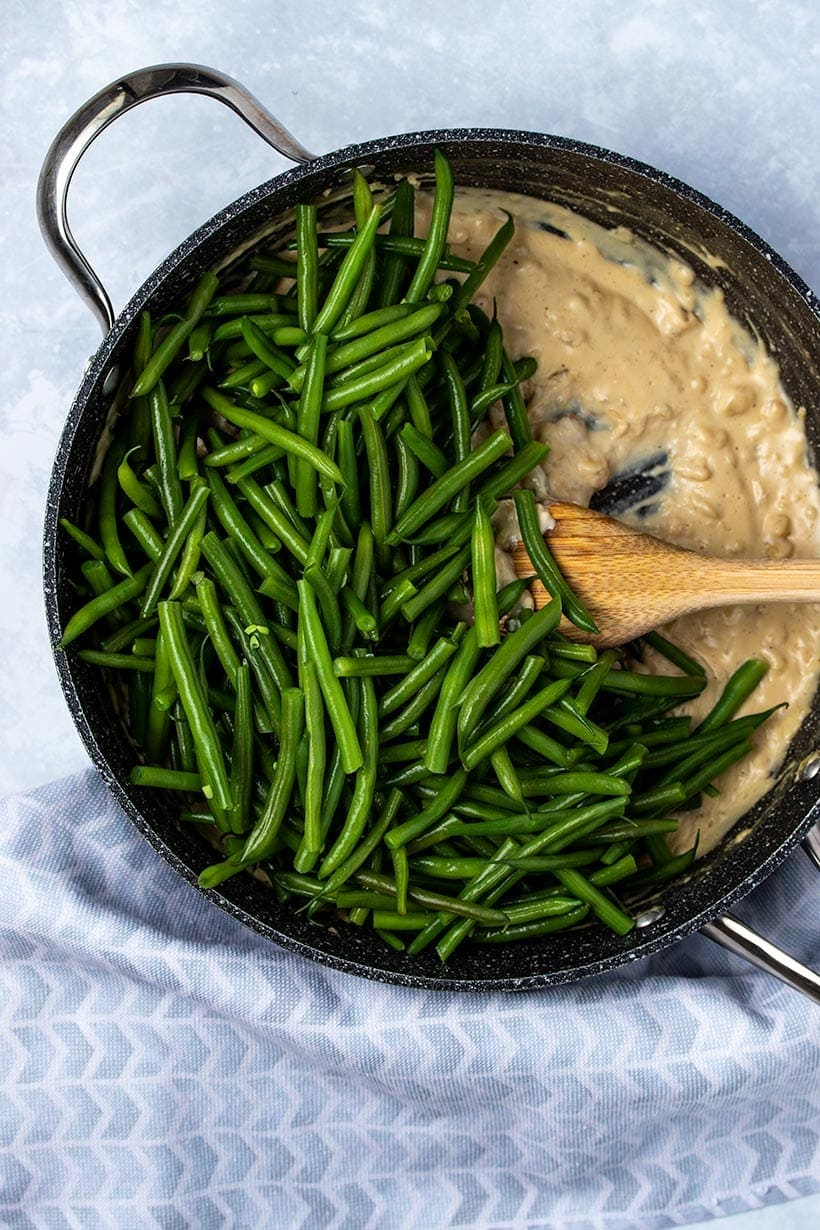 blanched green beans on top of cashew cream sauce in a black skillet next to a blue linen