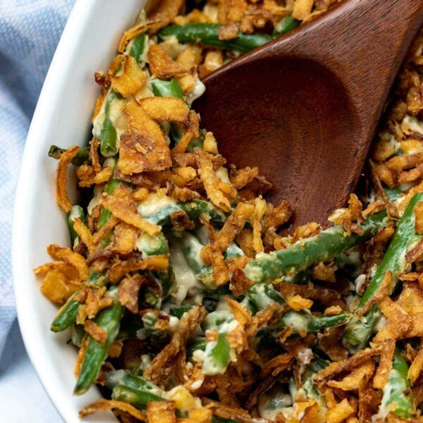 a wooden spoon taking a scoop of vegan green bean casserole
