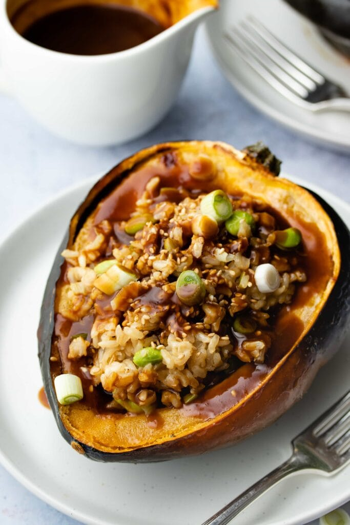 vegan stuffed acorn squash on a grey plate with a small white dish of miso maple gravy in the background