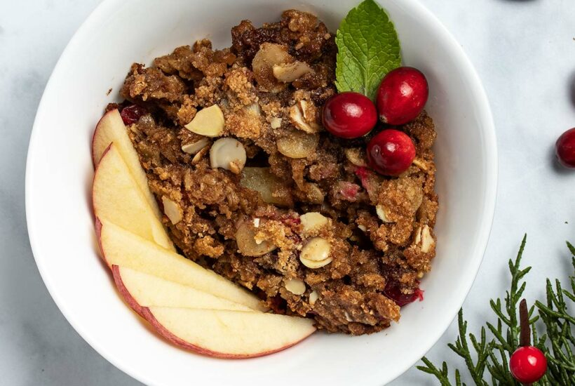 Cranberry Apple Baked Oatmeal in a white bowl garnished with sliced apple, cranberries and a mint leaf