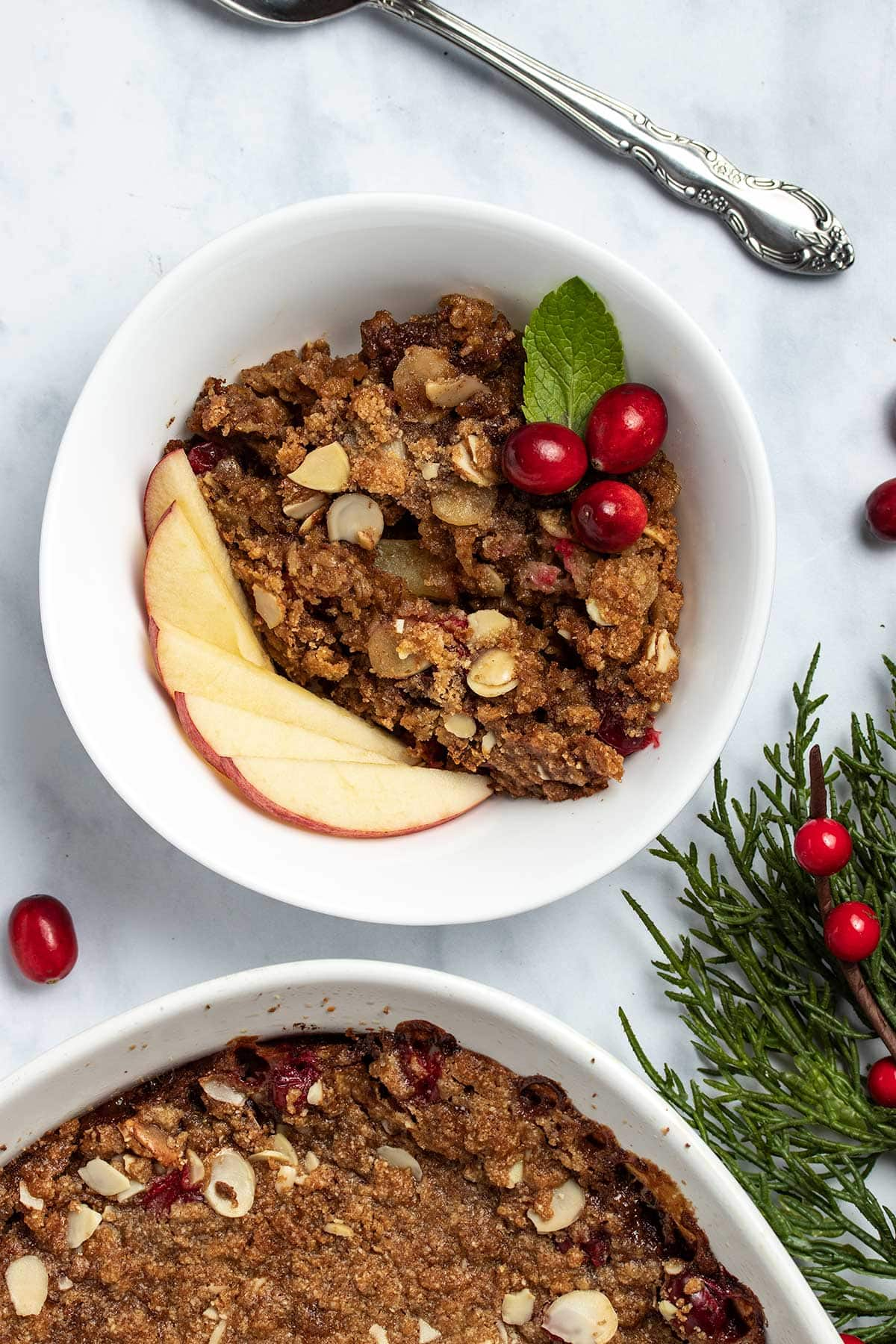 Cranberry Apple Baked Oatmeal in a white bowl garnished with sliced apple, cranberries and a mint leaf, next to baked oatmeal in a white casserole dish