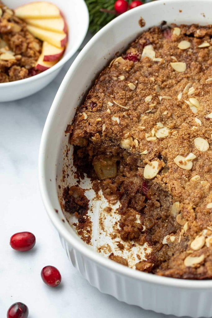 Cranberry Apple Baked Oatmeal in a white casserole dish with a scoop taken out