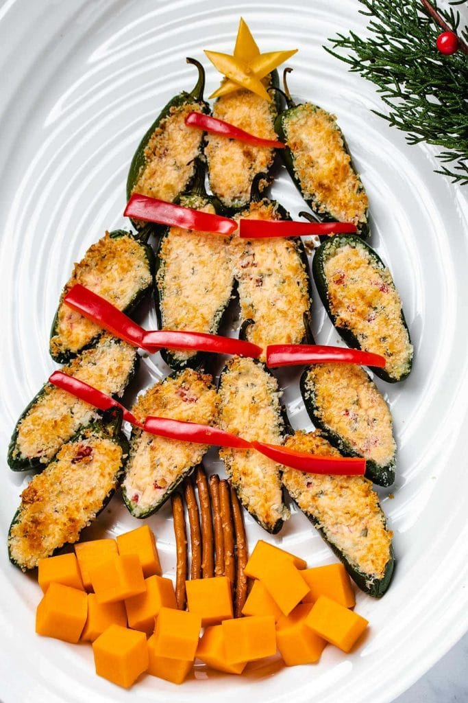 Jalapeno Poppers arranged into Christmas Tree shape with bell pepper decorations, pretzel trunk and cheddar cheese cube gifts