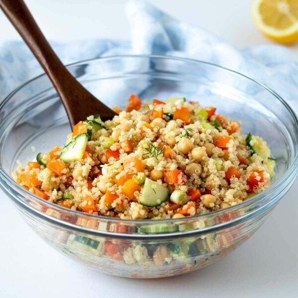 quinoa chickpea salad in large glass bowl with wooden spoon in front of a blue linen