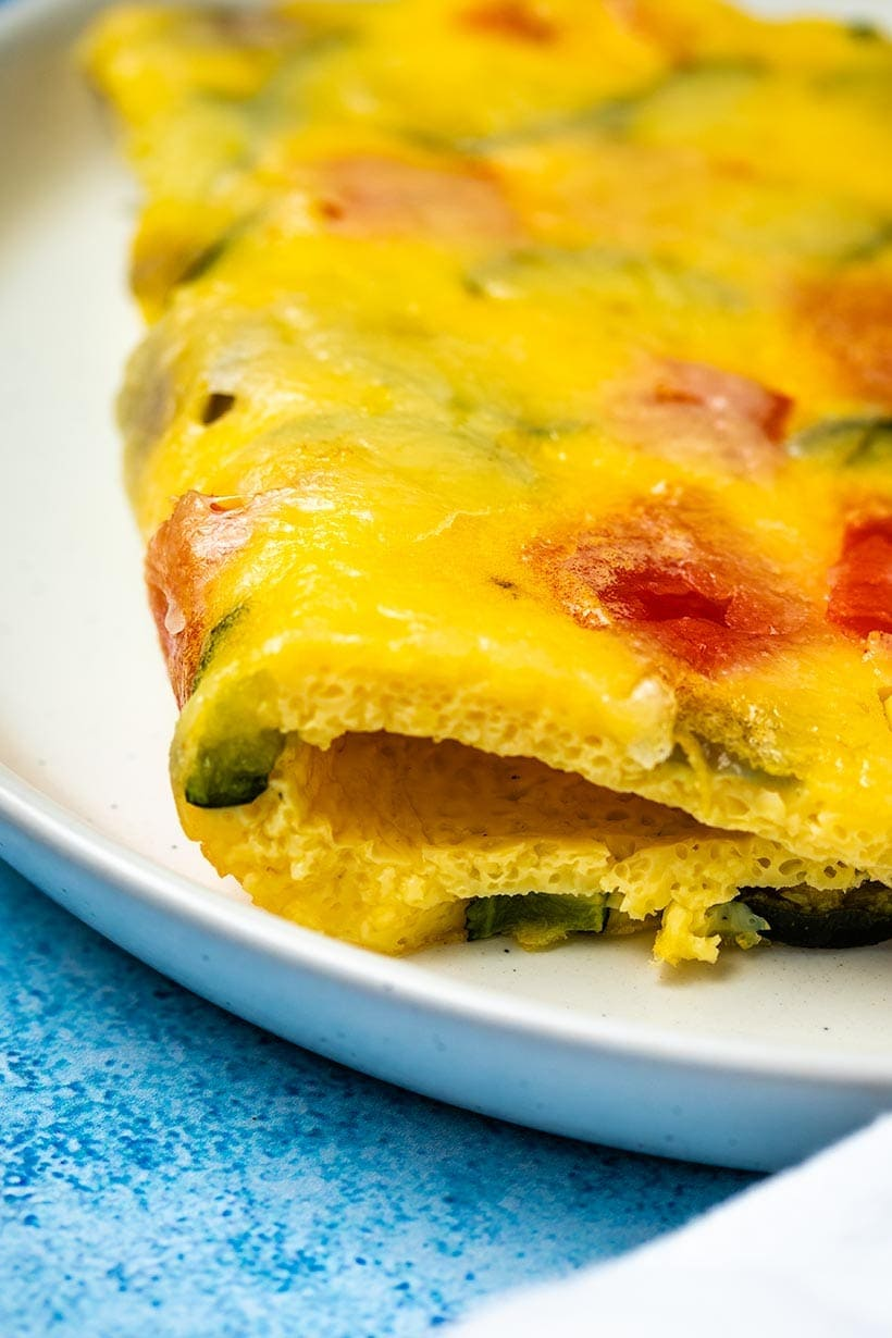 A folded slice of mixed vegetable sheet pan omelette on a white plate, viewed from the side to see the texture.