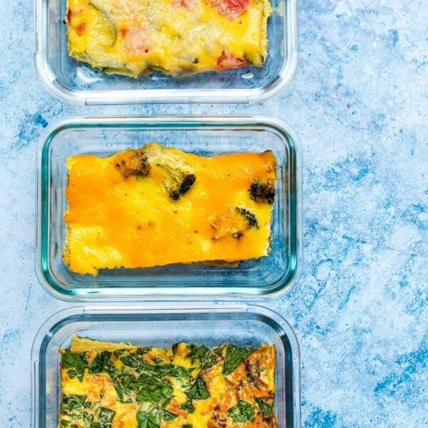 Three slices of roasted vegetable sheet pan omelette in glass meal prep containers