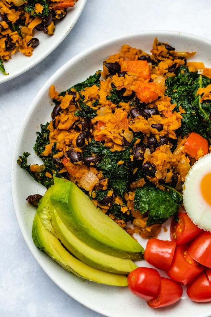 Sweet Potato, Kale and Black Bean Breakfast Skillet on a white plate served with avocado, sliced cherry tomatoes and an egg muffin