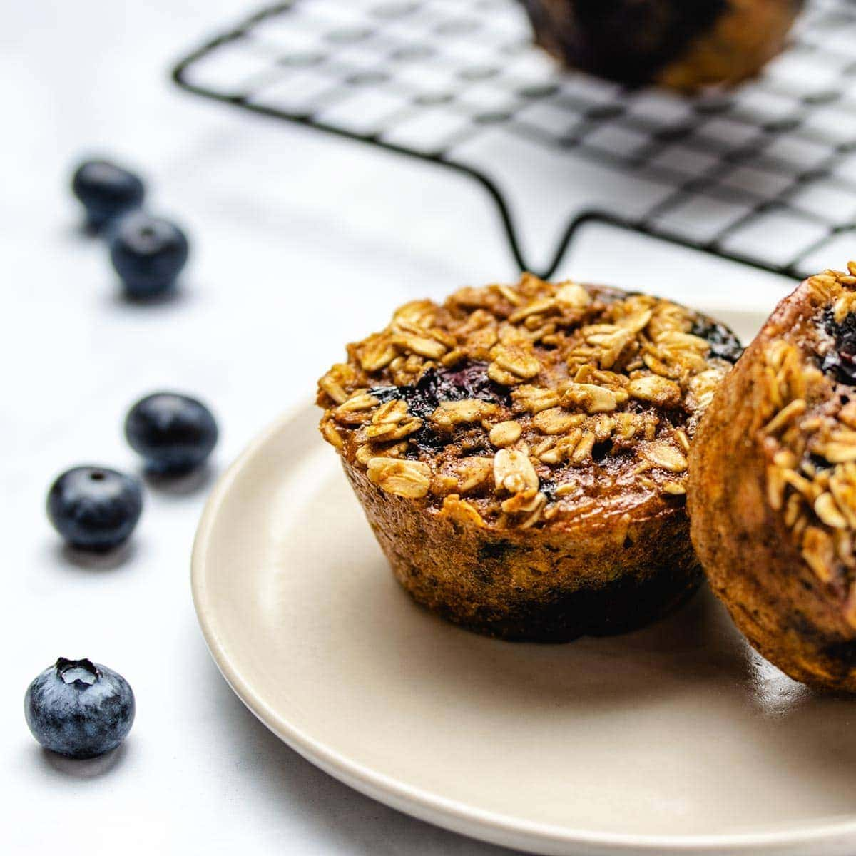 Two blueberry oatmeal cups on a cream coloured plate surrounded by fresh blueberries