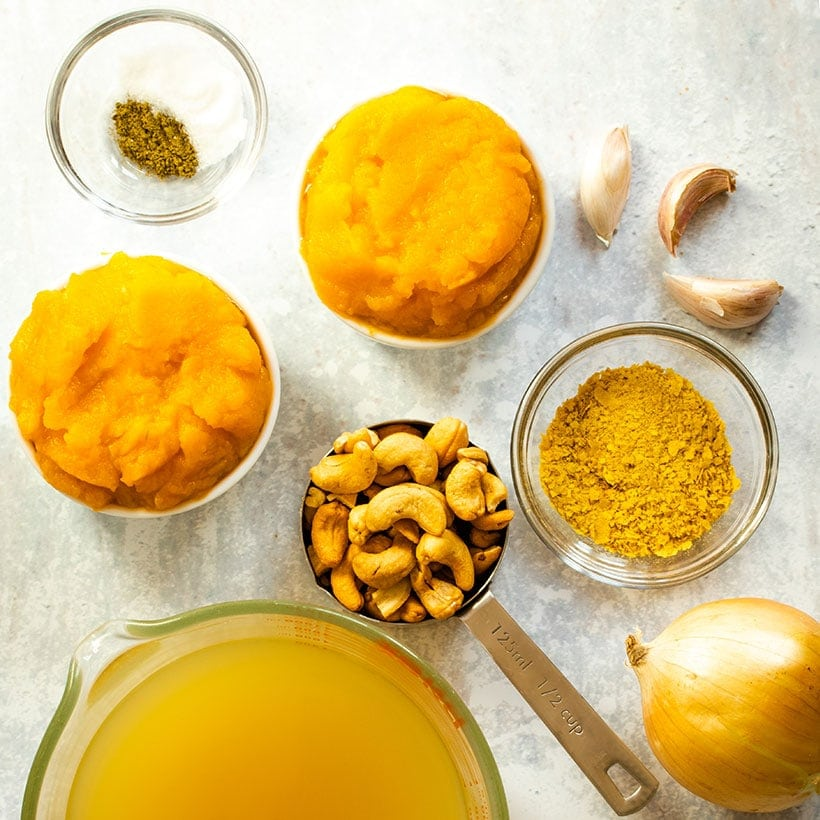 ingredients for vegan butternut squash sauce viewed from overhead on a grey background