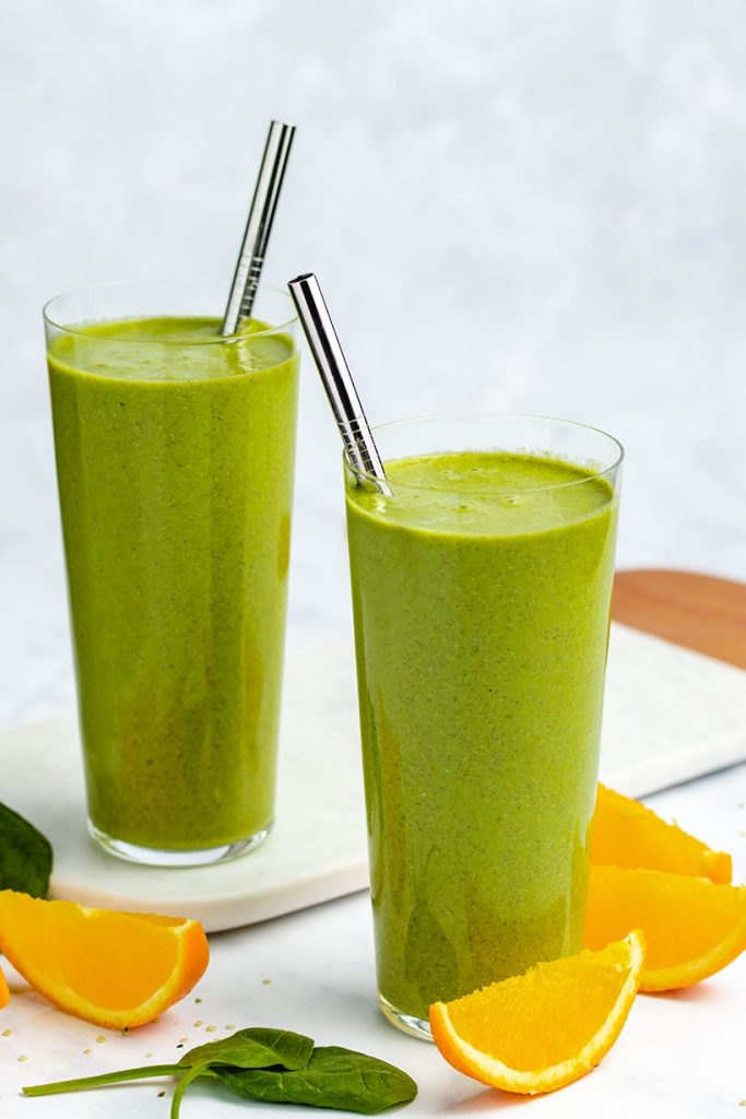 Green Orange and Ginger Smoothie in two tall glasses with metal straws surrounded by orange slices, spinach leaves and hemp hearts