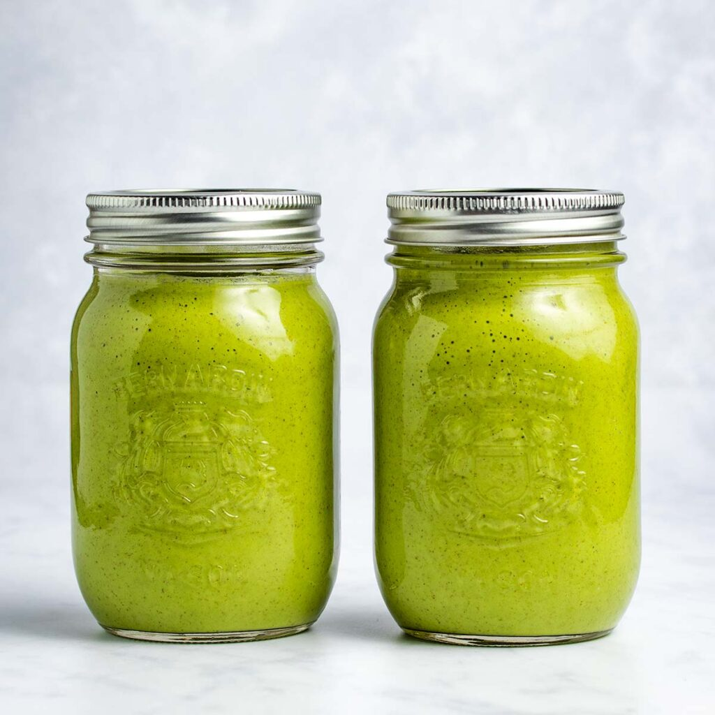 Two green smoothies in mason jars sitting side by side with a white background