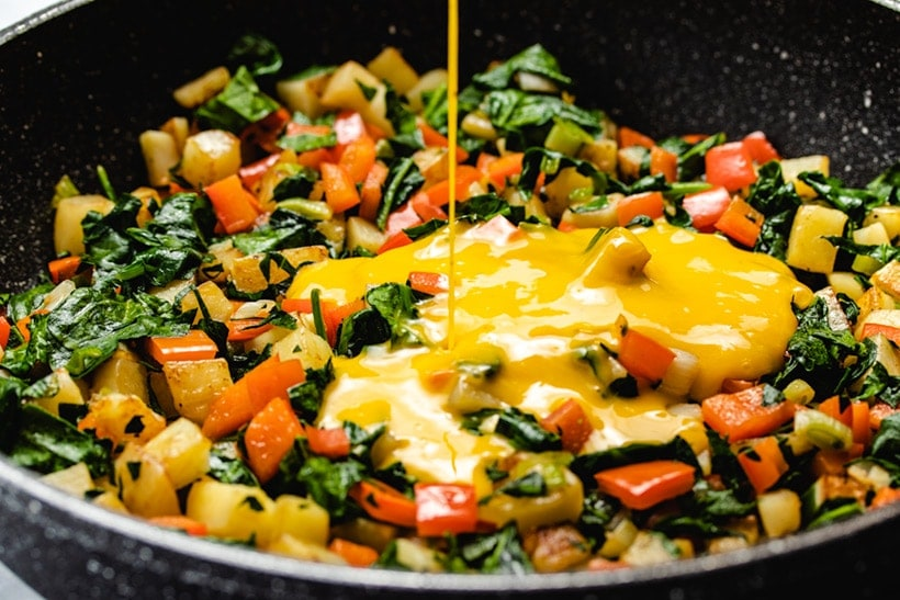 Whisked eggs being poured onto sautéed potato, red pepper, green onion and spinach in a black skillet