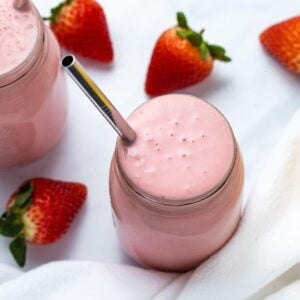 strawberry banana smoothie in a mason jar with a stainless steel straw with fresh strawberries in the background