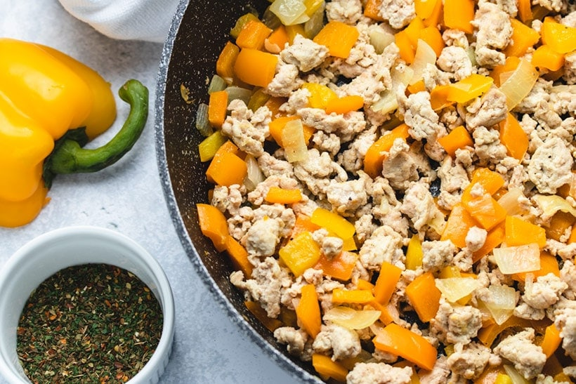 sauteed ground chicken and bell peppers in a black skillet next to a white bowl of spices and half a yellow bell pepper