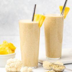 Two glasses of cauliflower smoothie garnished with pineapple and a silver straw surrounded by cauliflower florets, hemp hearts and a white bowl of diced pineapple